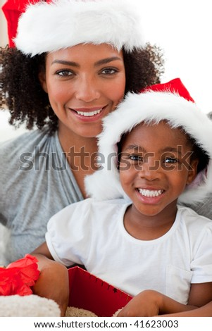 Smiling Afro-American mother and daughter opening a Christmas gift - stock photo