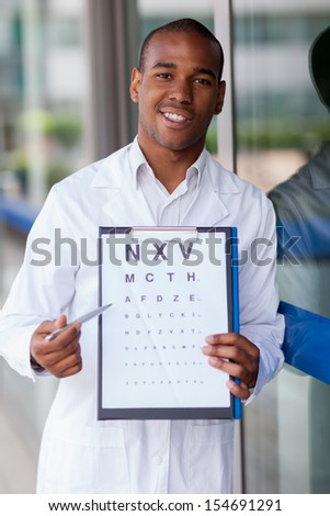 Smiling afro american oculist with flip chart - stock photo