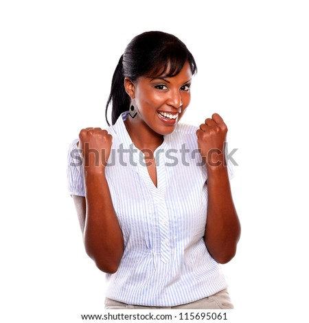 Smiling afro-american woman looking at you and celebrating a victory against white background - stock photo