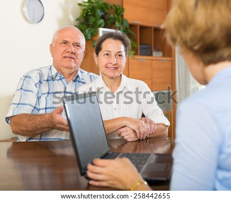 Smiling aged couple answer questions of social worker at home. Focus on woman  - stock photo