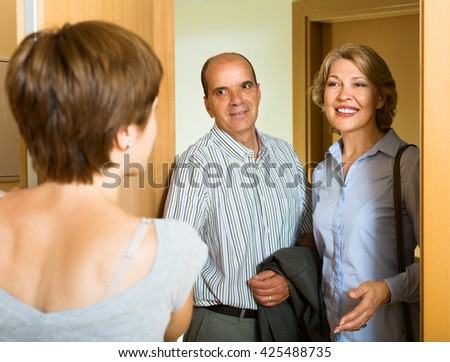 Smiling aged family couple visiting daughter at home
