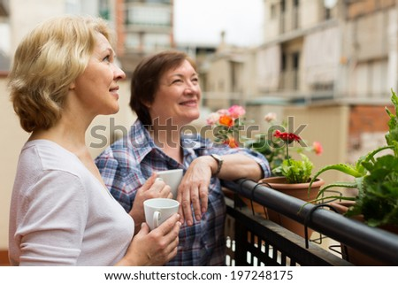 Smiling aged female friends relaxing with cup of coffee on balcony  - stock photo