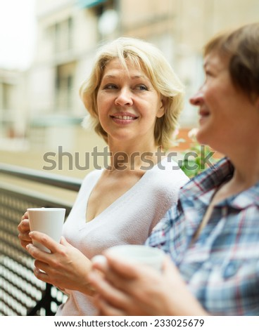 Smiling aged female friends staying on balcony with cup of coffee  - stock photo