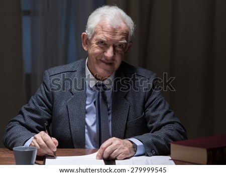 Smiling aged man working in the evening in his office - stock photo
