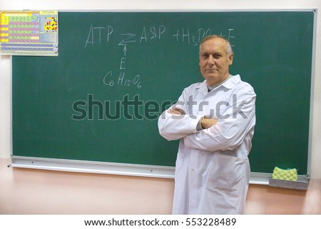 smiling aged teacher professor near the blackboard