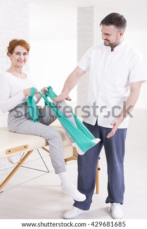 Smiling aged woman on rehabilitation sitting on a table and flexing her leg with elastic band. Next to her experienced therapist