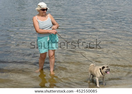Smiling aged woman with pug on a leash are standing in shallow of river water on riverbank. - stock photo