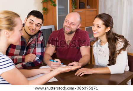 Smiling agent explaining to group of people the contract terms in living room - stock photo