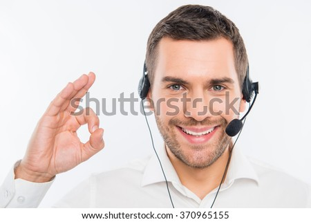 """Smiling agent of call centre gesturing """"OK"""" - stock photo"""
