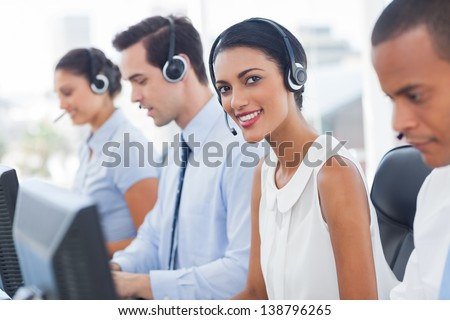 Smiling agent with colleagues sitting next to her - stock photo