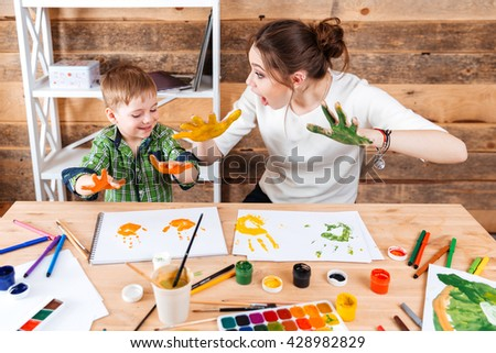 Smiling amazed young mother and her little son making prints by hands and paints on the paper  - stock photo