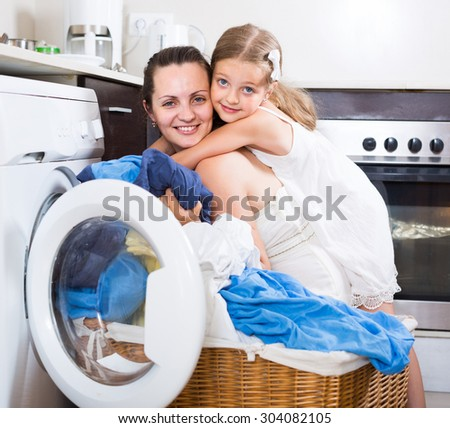 smiling american  housewife and her daughter with linen near washing machine  - stock photo
