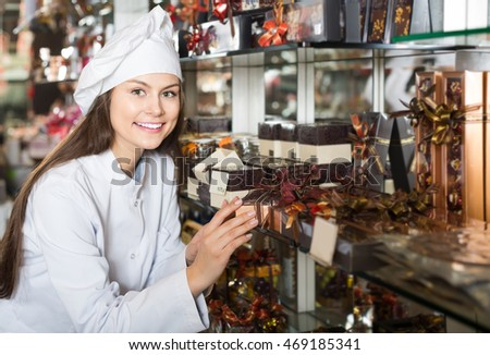 Smiling american  shopgirl posing with delicious ganaches, praline and chocolates