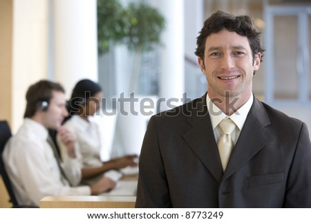 Smiling and confident businessman with seated colleagues behind him in the office