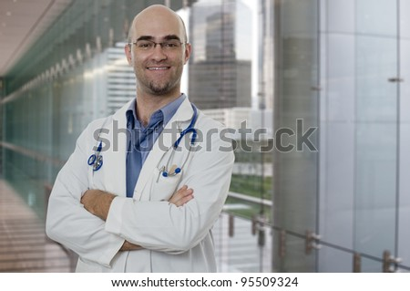 Smiling and confident Doctor standing with arms crossed - stock photo