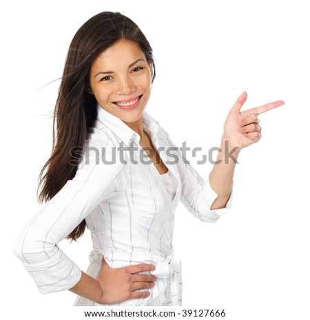 Smiling and confident woman in white pointing at your product while looking at the camera. Isolated on white background.Beautiful mixed asian / caucasian model. - stock photo