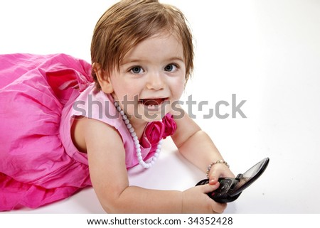 Smiling and Cute baby girl in red and pink dress using  a cell phone.