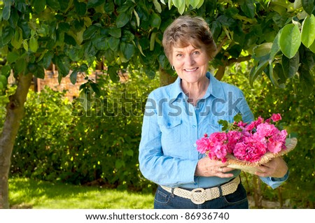 Smiling and Pretty Senior Woman Enjoying Her Garden and Holding a Bouquet of Pink or Red Roses that She Just Picked - stock photo