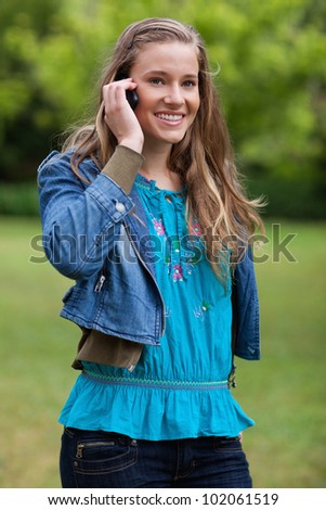 Smiling and relaxed teenager using her cellphone while standing in the countryside