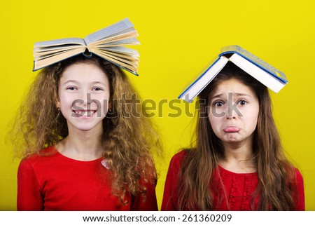 Smiling and Upset Two sisters , little schoolgirl  with book on their head, isolated over yellow background.  - stock photo