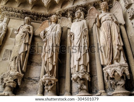 Smiling angel and the saints in the Cathedral Reims, France - stock photo
