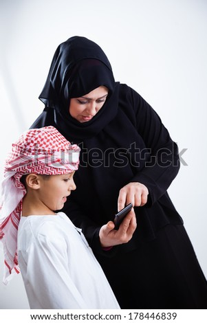 Smiling Arabic woman and her son using smart phone, isolated on white.