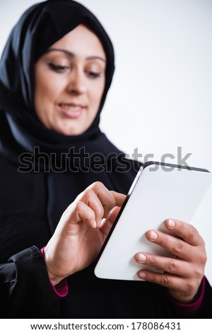 Smiling Arabic woman using digital tablet, isolated on white. - stock photo