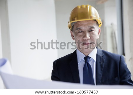Smiling architect in hardhat examining blueprint in office building - stock photo