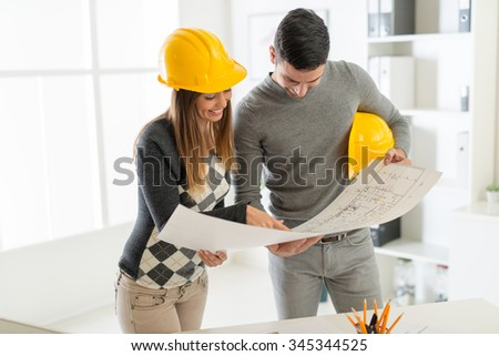 Smiling architect looking the architectural plans in office. - stock photo
