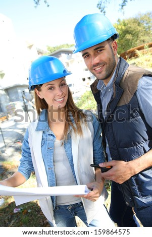Smiling architects standing on construction site - stock photo