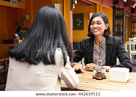 Smiling Asian business woman having a conversation with her female associate in a restaurant table - stock photo
