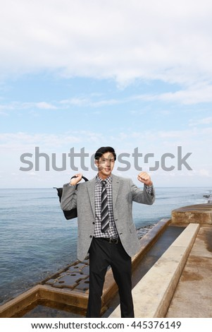 Smiling Asian businessman by the sea