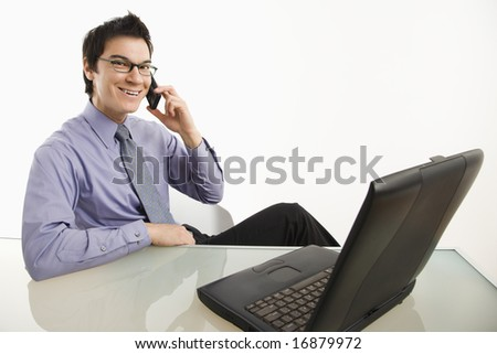 Smiling Asian businessman sitting at desk talking on cellphone.