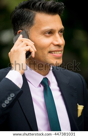 Smiling Asian Businessman Using Cell Phone