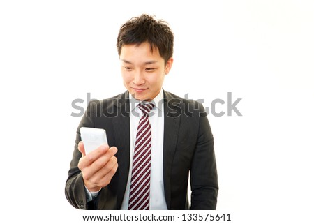 Smiling Asian businessman with sell phone - stock photo