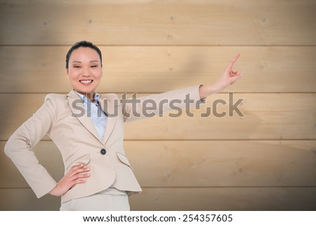 Smiling asian businesswoman pointing against bleached wooden planks background