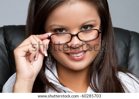 Smiling asian businesswoman wearing glasses - stock photo