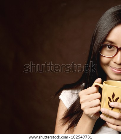 Smiling Asian / Caucasian Woman With Glasses. Girl holding and smelling a Mug of Coffee / Milk / Tea / Hot Chocolate. Brown Background. With Copy Space for Text. - stock photo