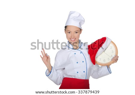smiling asian chef with clock and Christmas hat isolated in white - stock photo