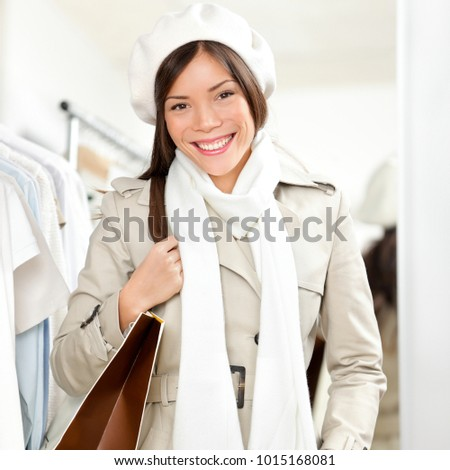 Smiling Asian customer in clothing store holding shopping bag wearing winter coat and scarf happy. Girl shopper portrait .