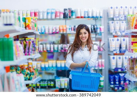 smiling asian girl holding shopping basket in hypermarket - stock photo