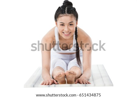 smiling asian girl in sportswear practicing forward bending pose on yoga mat isolated on white