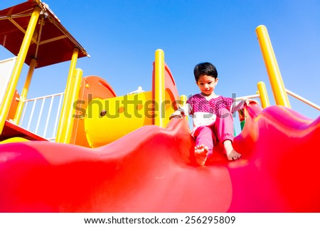 Smiling asian girl playing at playground during sunny day - stock photo