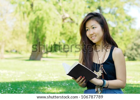 Smiling asian girl reading a book at the park