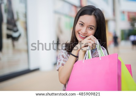 Smiling asian girl with shopping bags in shop