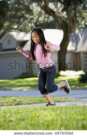 Smiling Asian girl, 7 years, playing on driveway outside house - stock photo