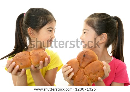 Smiling Asian girls holding a bread - stock photo