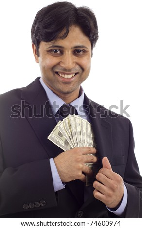 Smiling Asian - Indian businessman in a black suit putting money in his pocket isolated over white background