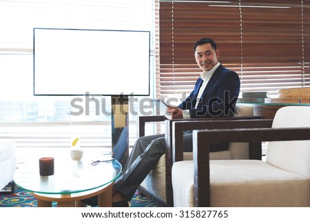 Smiling asian male entrepreneur working on touch pad while sitting in modern coffee shop near empty blank screen with copy space, successful man in elegant suit reading e-book on his digital tablet - stock photo