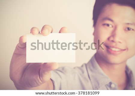 smiling asian man show blank card
